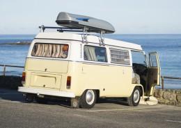 Surfer mit VW Bus vor der Bucht Sennen Cove in der Morgensonne, Cornwall, UK