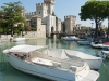 Mit einem Boot lässt sich die Wasserburg von Sirmione und die Halbinsel erkunden, Gardasee, Italien