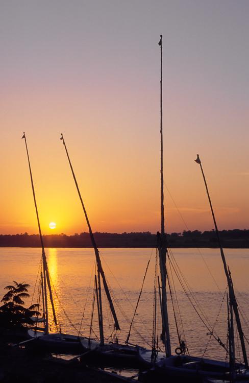 Feluken liegen am Ufer des Nils bei Luxor bei Sonnenuntergang,