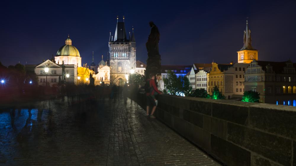 Menschen flanieren über die Karlsbrücke bei Nacht, Prag, Tschechien