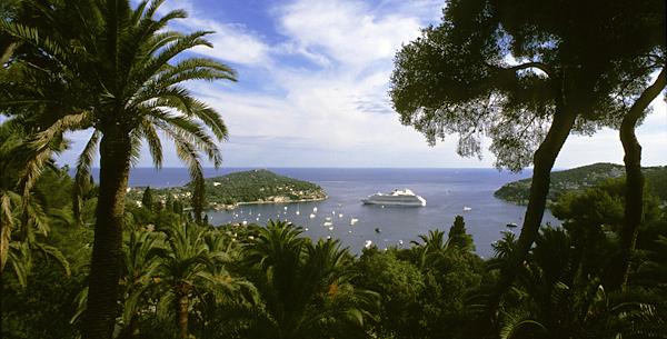 Blick durch Palmen auf das Cap Ferrat mit der Villa Ephrussi de Rothschild und die Bucht von Villefranche, Cote d'Azur, Frankreich