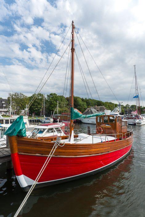 Fischerboot aus Holz mit rotem Rumpf im Hafen von Kloster auf der Insel Hiddensee
