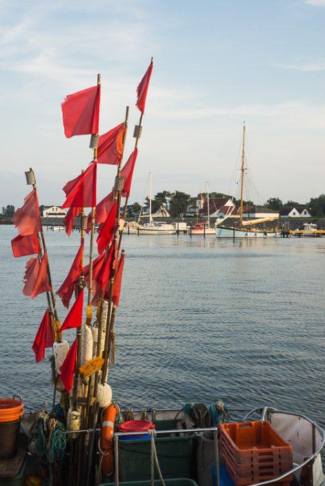 Flaggen und Bojen für Fangnetze auf einem Fischerboot auf Hiddensee