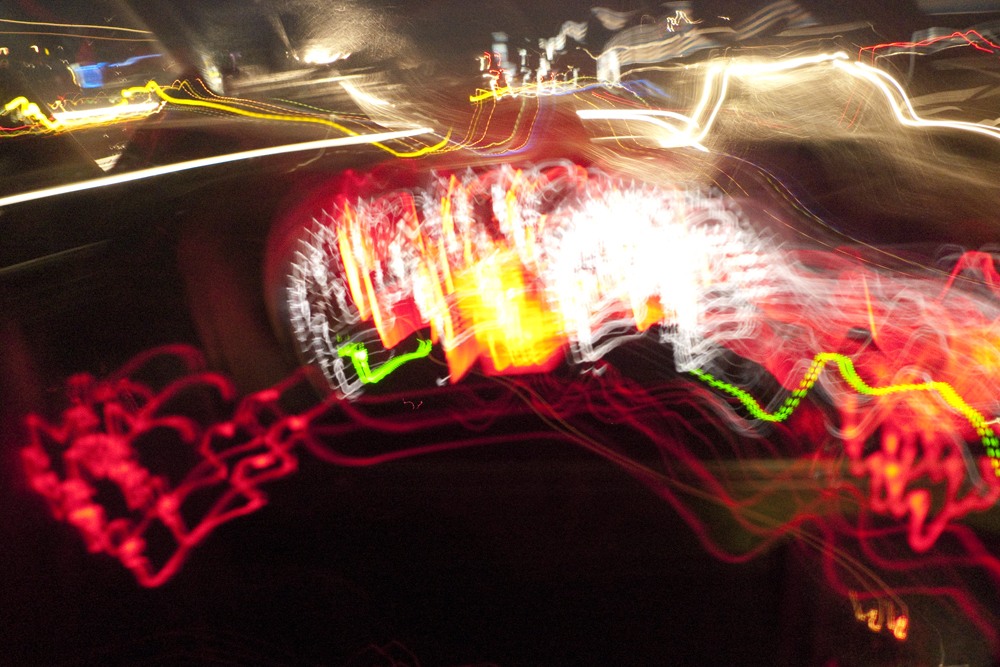 Die Lichter des Autocockpit und der Strasse bei Nacht verschmelzen zu einem Lichtgemälde