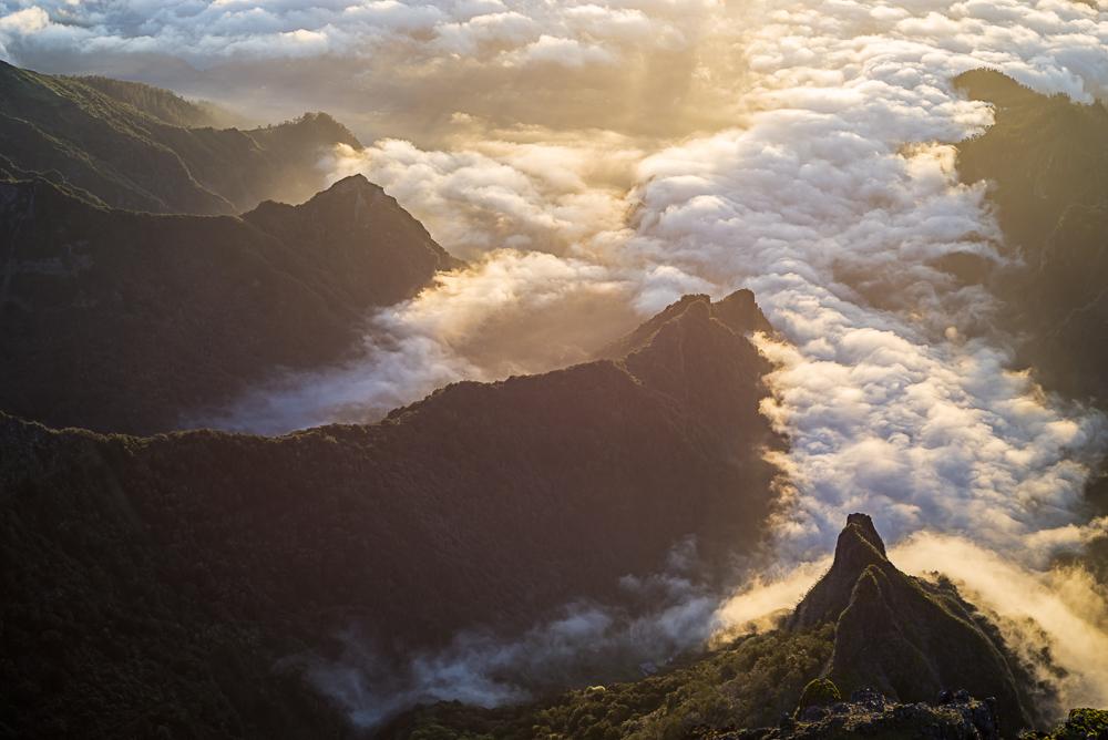 Niedrige Wolken hängen beim Sonnenaufgang über Madeira noch im Tal von Faja da Nogueira, weit unterhalb des Gipfels des Pico do Arieiro