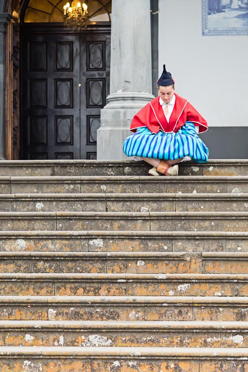 Vor der Wallfahrtskirche von Monte in Funchal, Madeira, sitzt eine Frau einer traditionellen Musikgruppe auf der Treppe und wartet auf ihr Konzert zur Feier des 500-jährigen Bestehens des Bistums Funchal