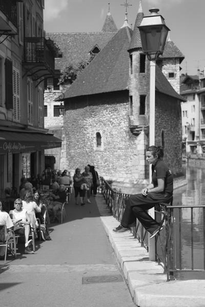 Straßenszene vor einem Café in der Altstadt von Annecy mit dem Palais d'Isle und dem Fluss Thiou, Frankreich