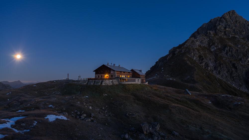Vollmond und Morgendämmerung über der Fiderepasshütte im Allgäu, Deutschland