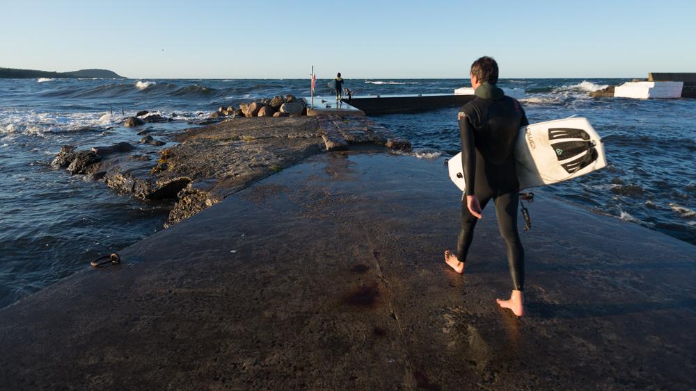 Surfer auf der Hafenmole von Vik, Schonen, Schweden