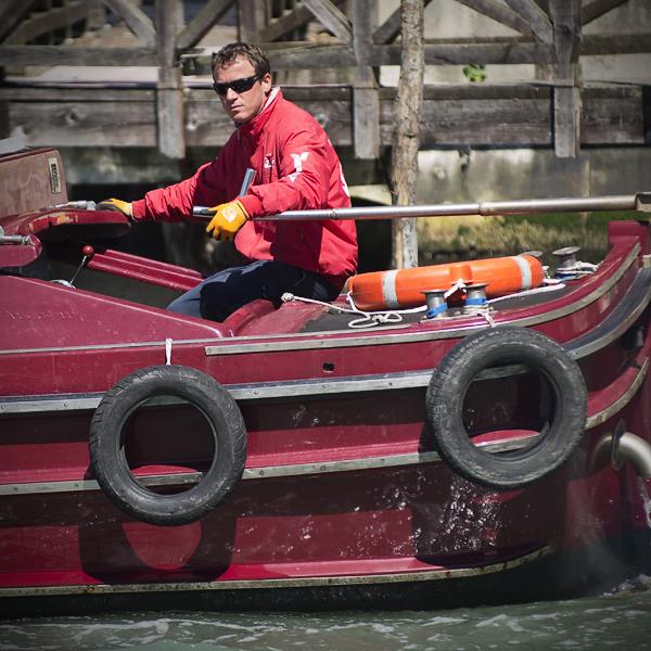 Bootsführer eines Frachtkahns auf dem Canal Grande, Venedig, Italien