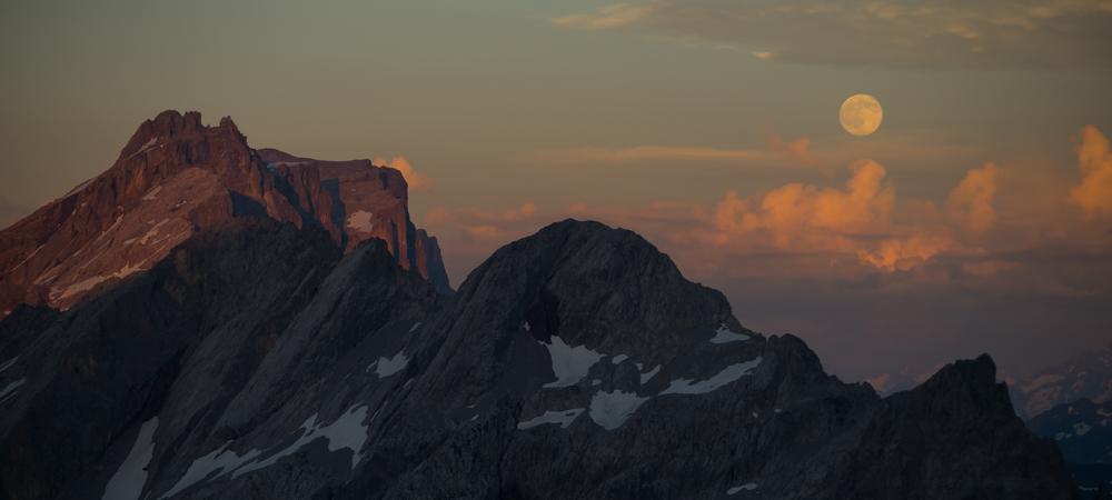 Aufgang des Vollmonds im letzten Sonnenlicht über dem Rätikon, Vorarlberg, Österreich