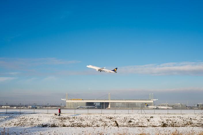 Spaziergänger mit Hund vor startendem Flugzeug und Hangar am Flughagen München