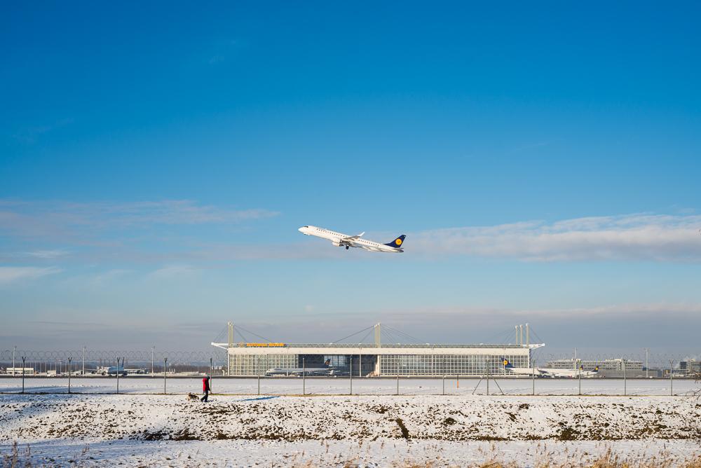 Spaziergänger mit Hund vor startendem Flugzeug und Hangar am Flughafen München