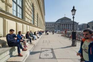 Menschen sitzen vor der Münchner Residenz uns geniessen die Frühlingssonne