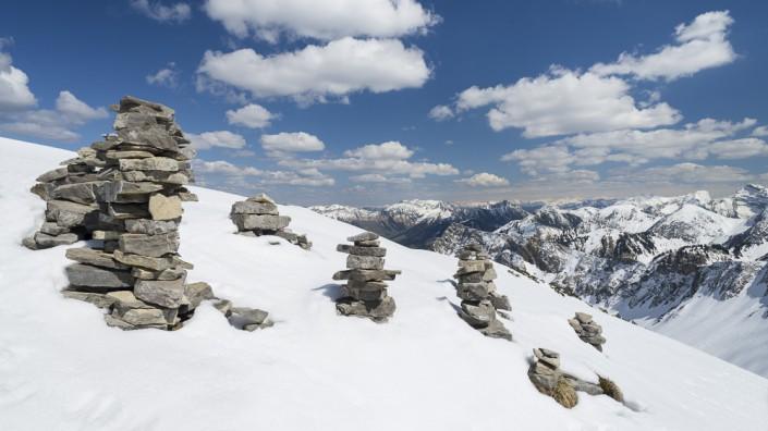 Steinmänner am Schafreiter vor dem Panorama der schneebedeckten Berge des Karwendel