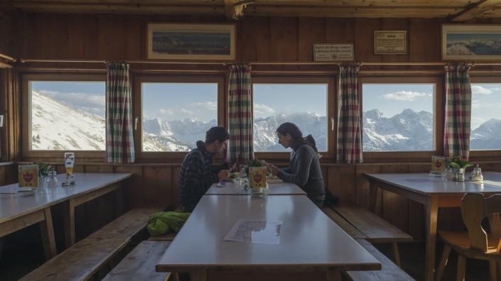 Junges Paar beim Abendessen auf der Tölzer Hütte