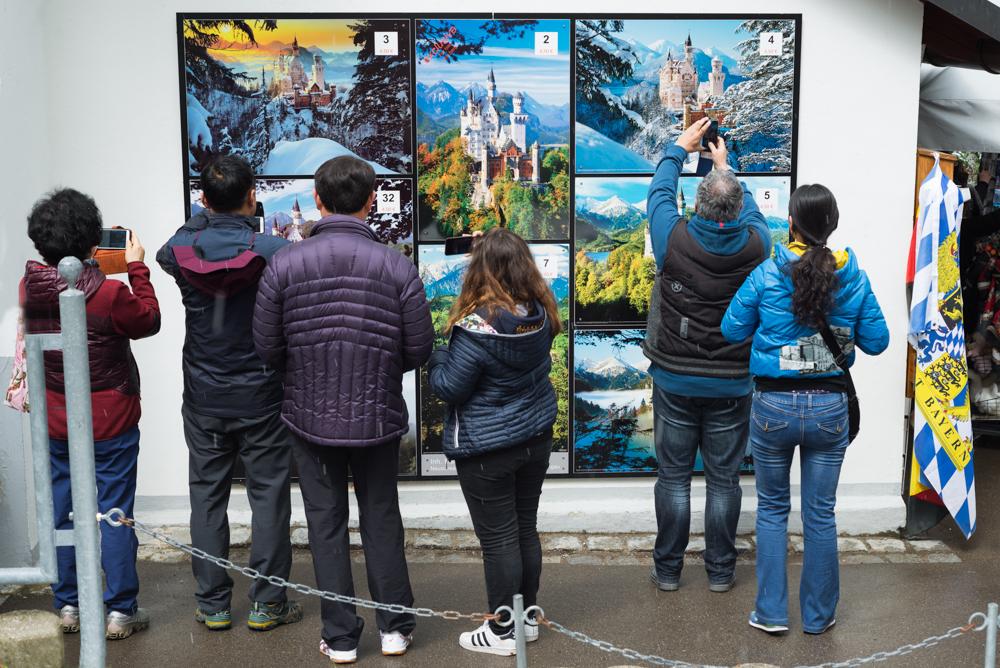 Touristen fotografieren die Bilder auf einem Werbeplakat für Drucke vom Schloss Neuschwanstein, Bayern, Deutschland