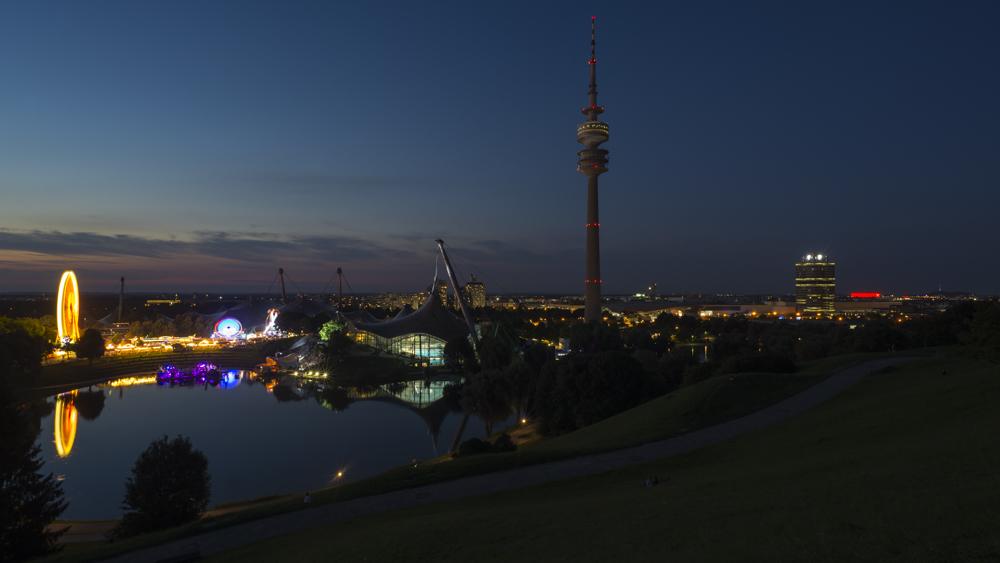 Olympiaturm und Olympiastadion mit dem Sommerfestival im Olympiapark von München in der Abenddämmerung