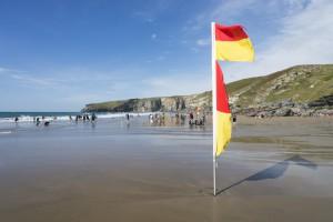 Fahne der Strandwache am nur bei Ebbe sichtbaren Sandstrand von Trebarwith, Cornwall, UK