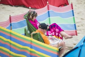 Urlauber am Strand von St. Ives mit buntem Windschutz, Cornwall, UK