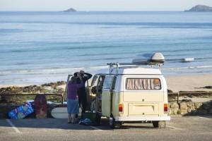 Surfer mit VW Bus vor der Bucht Sennen Cove in der Morgensonne,