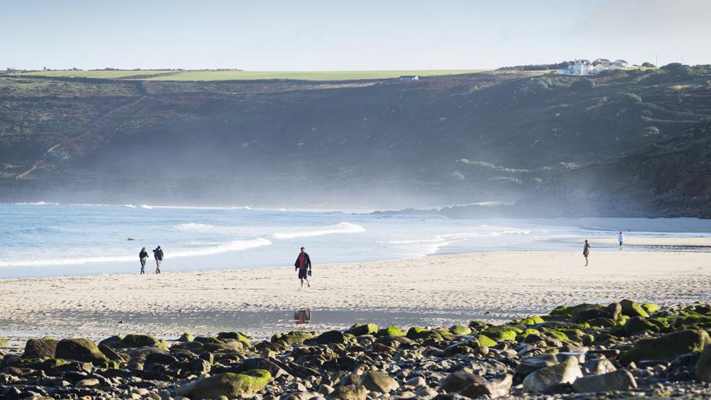 Strandwanderer bei Ebbe am Sandstrand von Sennen Cove, Cornwall, UK