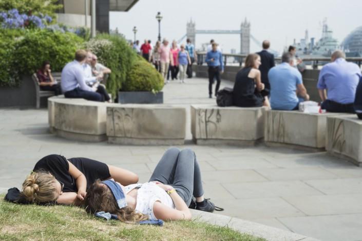 Während der Mittagspause sitzen und essen Menschen am Themseufer in London