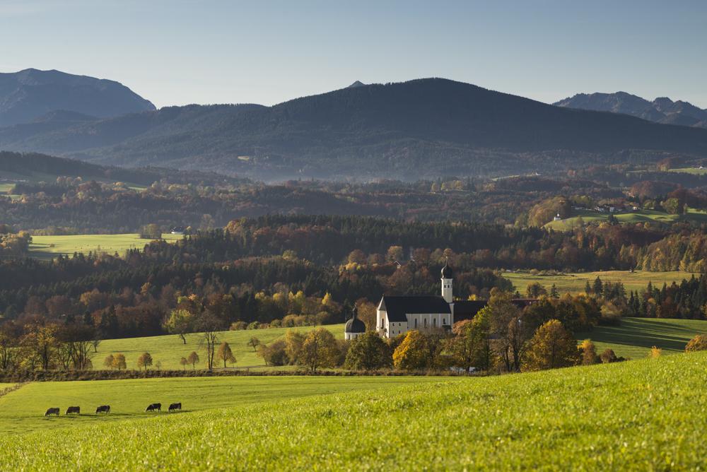 Die Wilpartinger Wallfahrtskirche vor den bayrischen Alpen im Herbst in der Morgensonne, Bayern, Deutschland