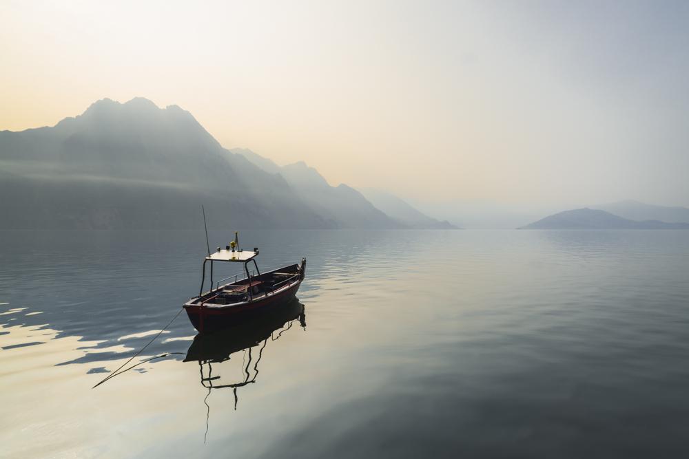 Boot auf dem Iseosee vor Panorama mit Bergen und der Monte Isola im Morgendunst