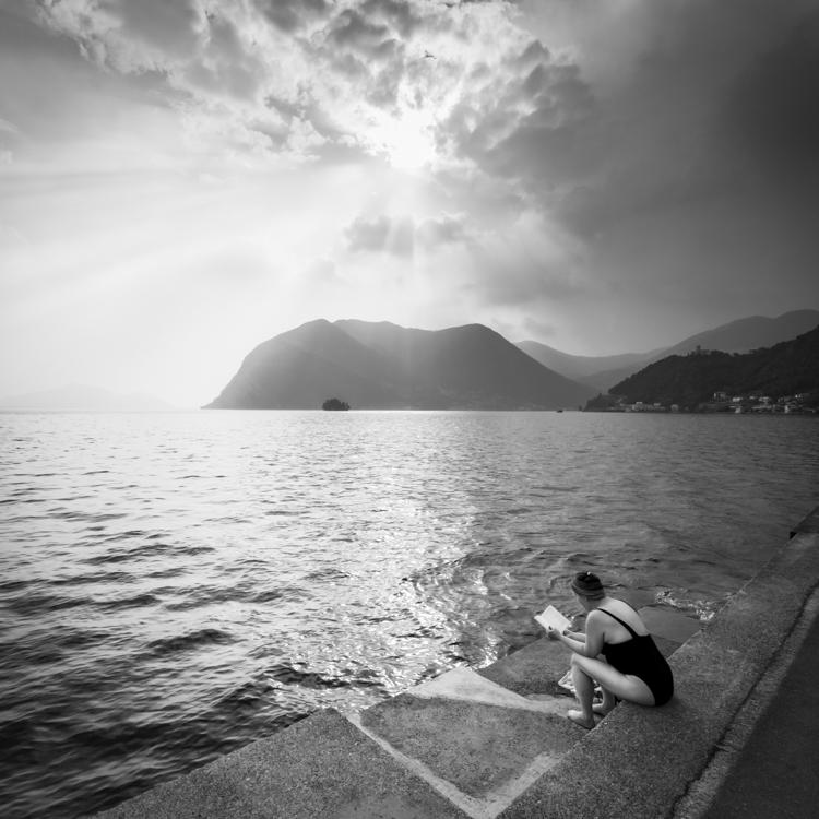 Frau sitzt im Badeanzug am Ufer der Monte Isola im Iseosee in den letzten Sonnenstrahlen vor einem heraufziehenden Gewitter und liest