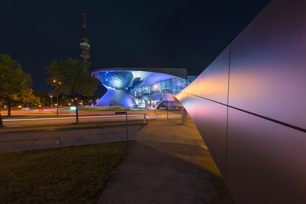 Beleuchtete Fassade der BMW Welt mit der Fußgängerbrücke vor dem Olympiaturm bei Nacht, München, Bayern, Deutschland