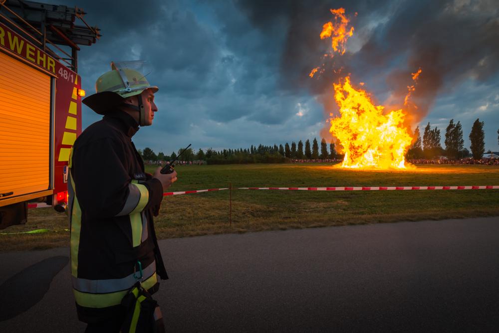 Ein Feuerwehrmann beobachtet die großen Flammen des Sonnwendfeuers der Freiwilligen Feuerwehr Hallbergmoos