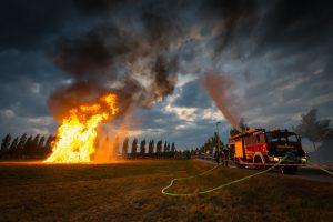 Feuerwehr pritzt Wasser gegen Funkenflug von den großen Flammen des Sonnwendfeuers der Freiwilligen Feuerwehr Hallbergmoos