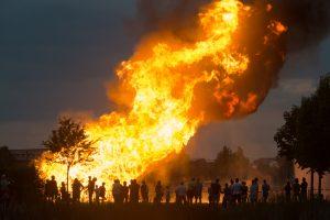 Zuschauer blicken in die großen Flammen des Sonnwendfeuers der Freiwilligen Feuerwehr Hallbergmoos