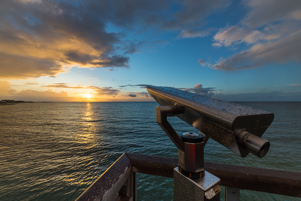 Fernrohr aus Edelstahl mit Wassertropfen auf der Seebrücke von Heiligenhafen vor dem Sonnenuntergang über der Ostsee