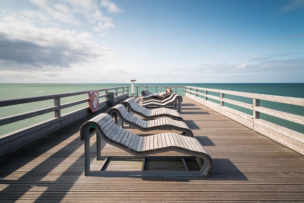 Menschen sonnen sich auf den Liegestühlen auf der Seebrücke von Heiligenhafen an der Ostsee, Schleswig-Holstein, Deutschland