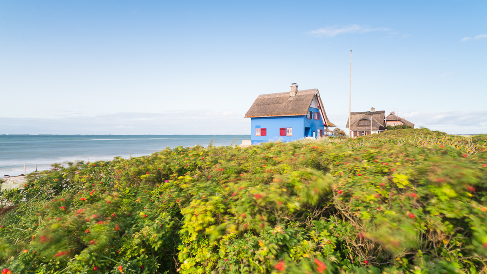 Historisches Strandhaus mit blauer Fassade und Reetdach auf der Halbinsel Graswarder an der Ostseeküste bei Heiligenhafen in Schleswig-Holstein, Deutschland