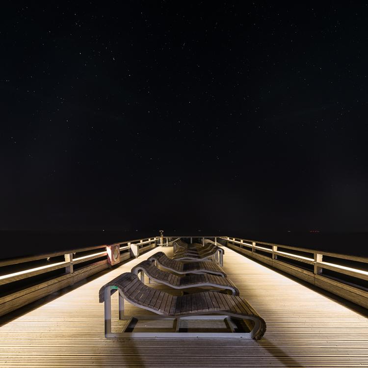 Sternenhimmel über der beleuchteten Seebrücke von Heiligenhafen an der Ostsee, Schleswig-Holstein, Deutschland