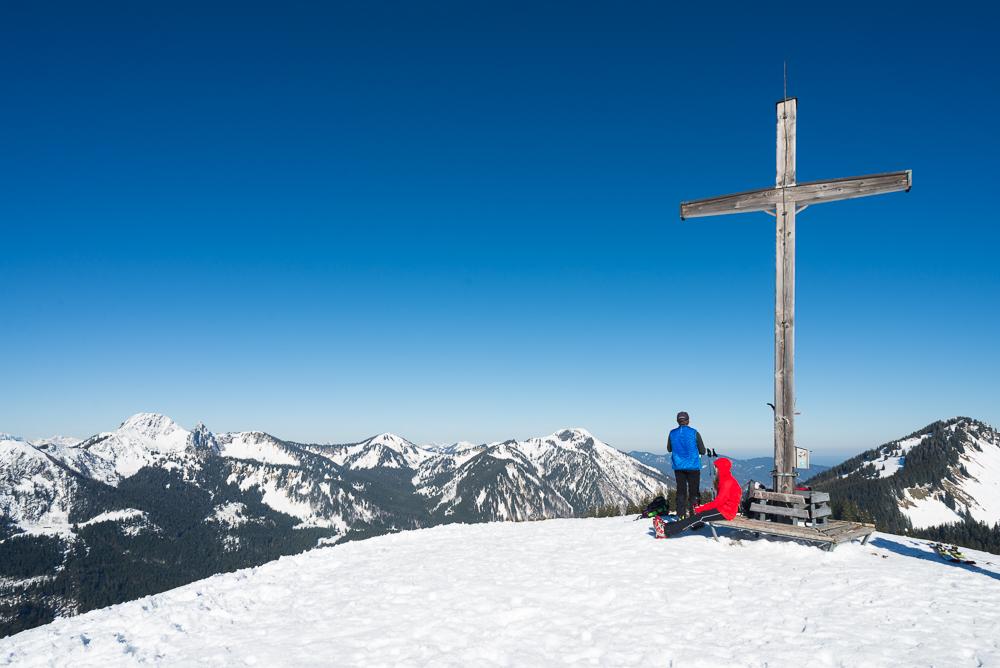Skitourengeher rasten am Gipfelkreuz des Rosskopf vor dem Panorama der bayrischen Alpen (Risserkogel, Plankenstein,Wallberg), Bayern, Deutschland