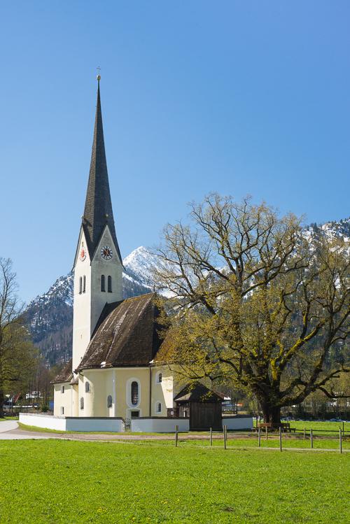 Die Kirche St. Leonhard am Schliersee vor Schneebergen und austreibenden Blättern an Bäumen in der Frühlingssonne, Bayern Deutschland