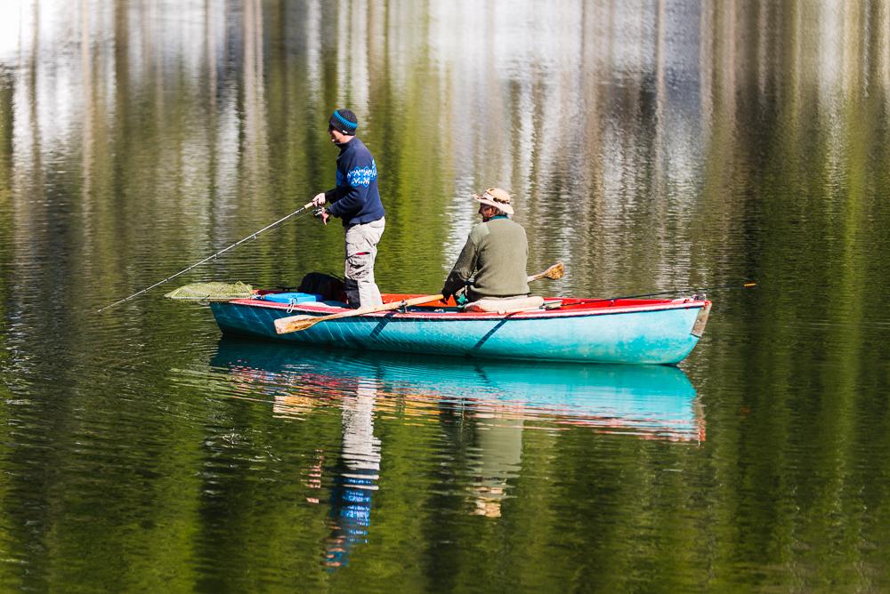 Zwei Angler in einem Ruderboot auf dem schon eisfreien Spitzingsee im Frühling, Bayern,Deutschland