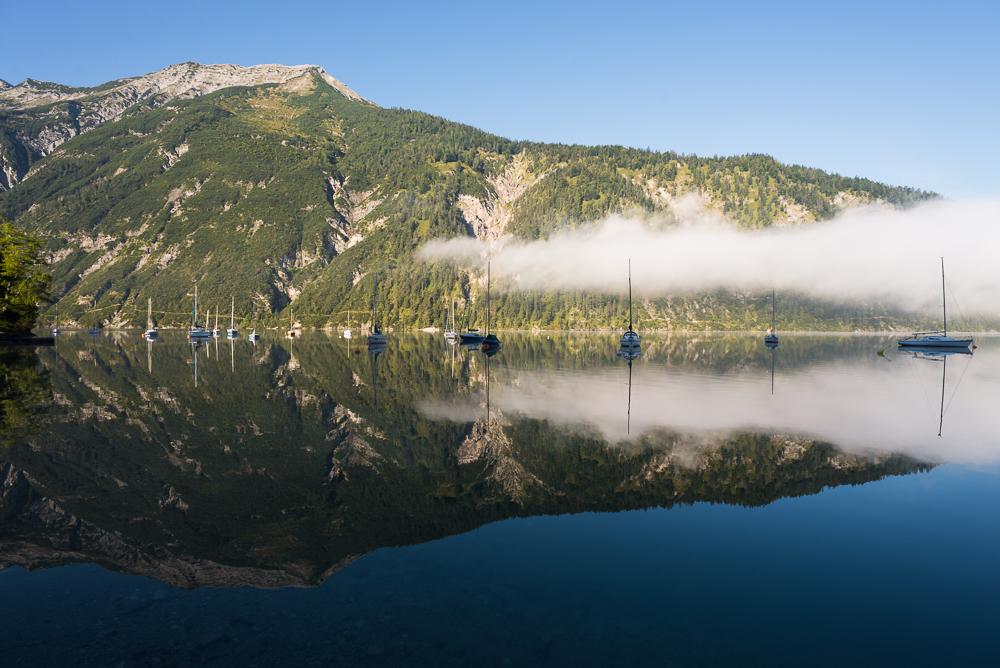 Die Seekarspitze und Segelboote in der Morgensonne spiegeln sich in der Oberfläche des Achensee, Tirol, Österreich