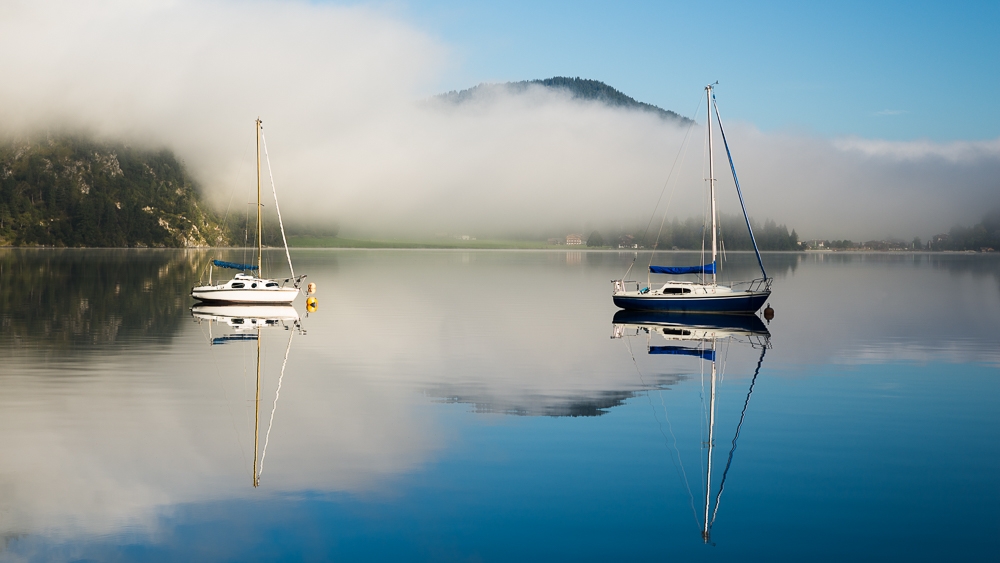 Nebelschwaden, Berge und Segelboote in der Morgensonne spiegeln sich in der Oberfläche des Achensee, Tirol, Österreich