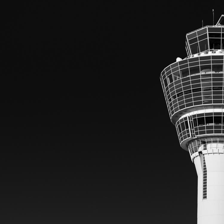 Weißer Kontrollturm (Tower) des Flughafen München MUC in der Morgensonne vor blauem wolkenlosem Himmel, Bayern, Deutschland
