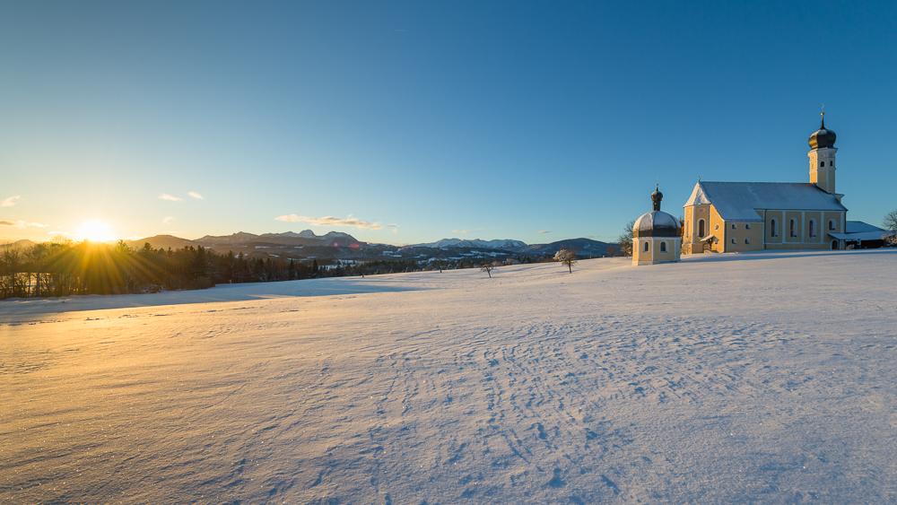 Die barocke Wallfahrtskirche Wilparting im ersten Sonnenlicht bei Sonnenaufgang an einem verschneiten Wintermorgen, Bayern, Deutschland