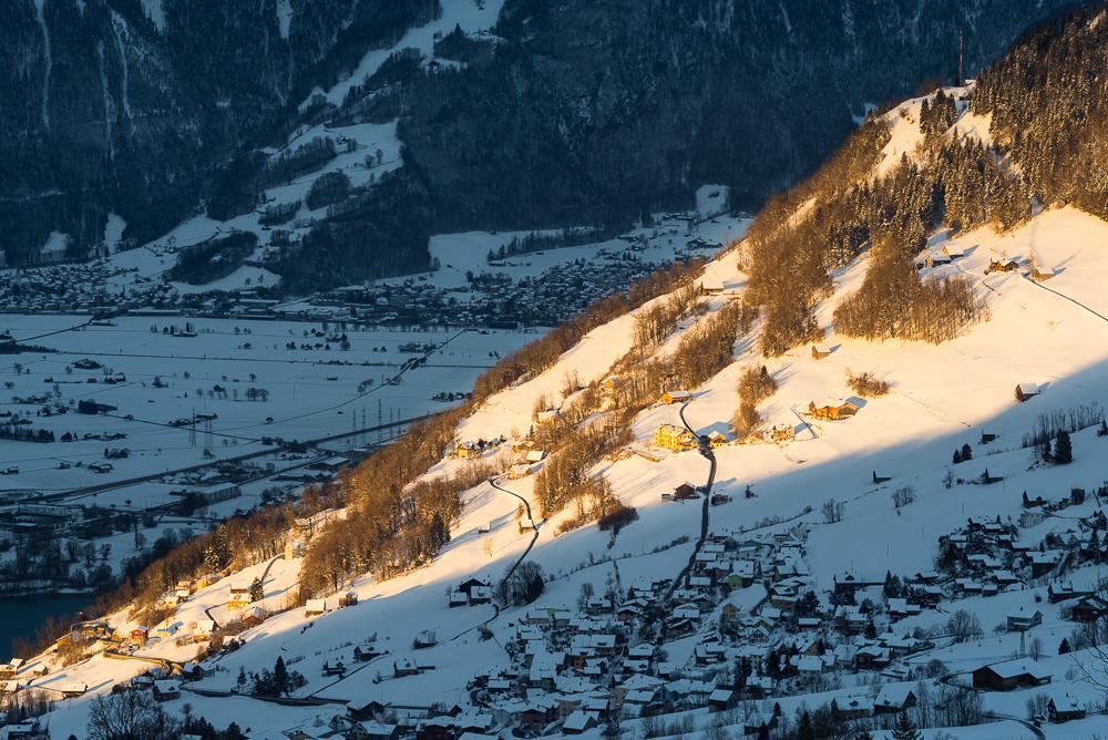 Ein Streifen Sonnenlilcht scheint auf die Hänge von Amden oberhalb des Walensees, Glarus, Schweiz