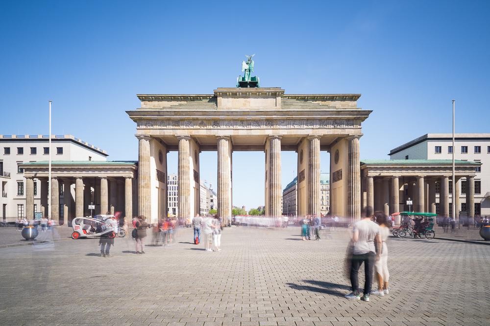 Menschen strömen an einem sonnigen Frühlingstag durch das das Brandenburger Tor in Berlin