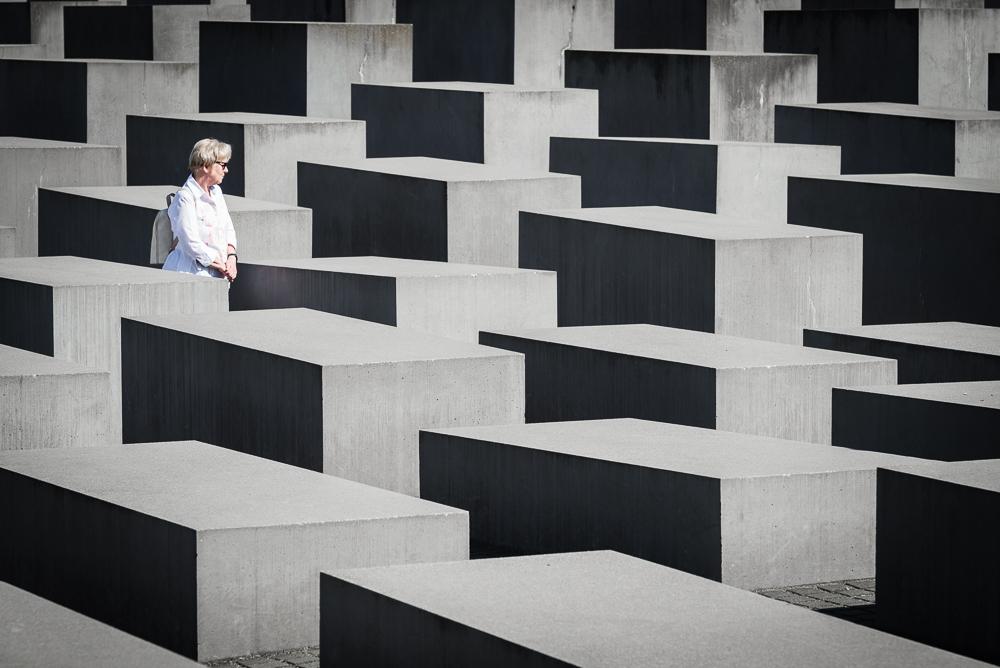 Frau zwischen den Blöcken des Holocaust Mahnmals, Berlin, Deutschland
