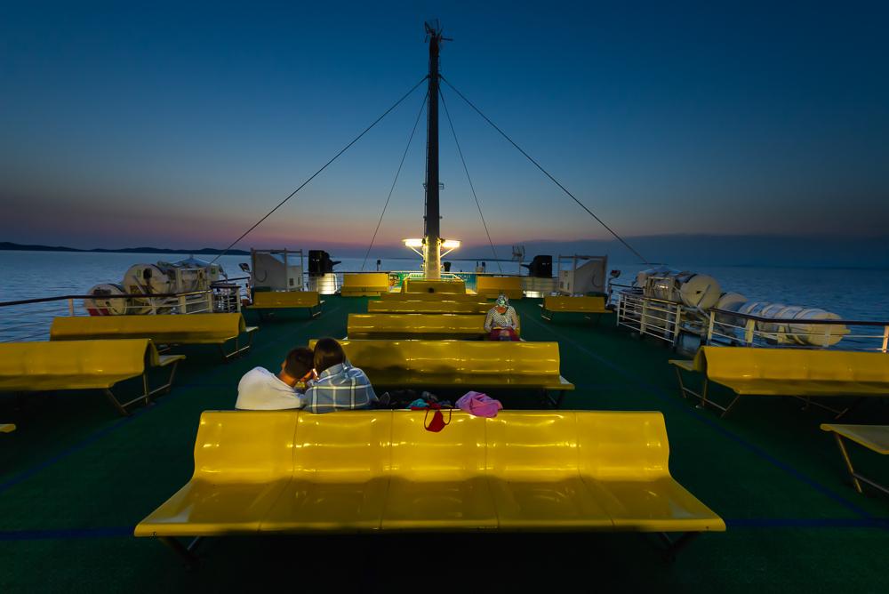 Passagiere sitzen auf gelben Sitzreihen auf dem Oberdeck einer Fähre im Archipel von Zadar nach Sonnenuntergang in der Dämmerung, Kroatien