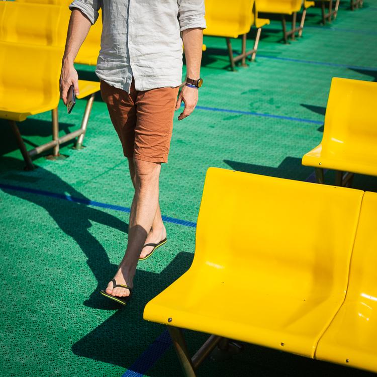 Mann im Shorts und mit Flip-Flops läuft auf grünem Boden zwischen den gelben Sitzbänken auf dem Oberdeck einer Jadrolinija Fähre in Kroatien